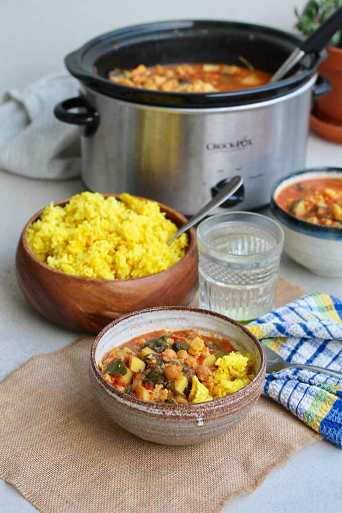 A bowl of chickpea curry with golden rice and a slowcooker in the background