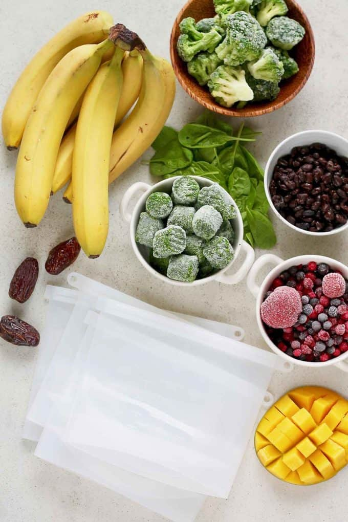 fresh and frozen fruits and vegetables and silicon freezer bags on a grey surface