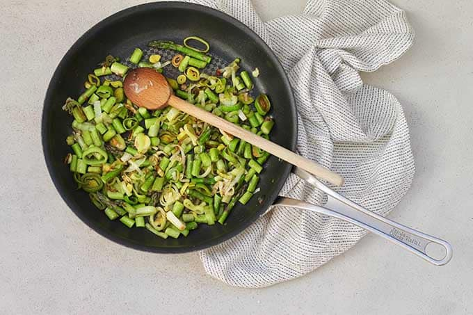 Pan fried asparagus and leeks in a non-stick frying pan