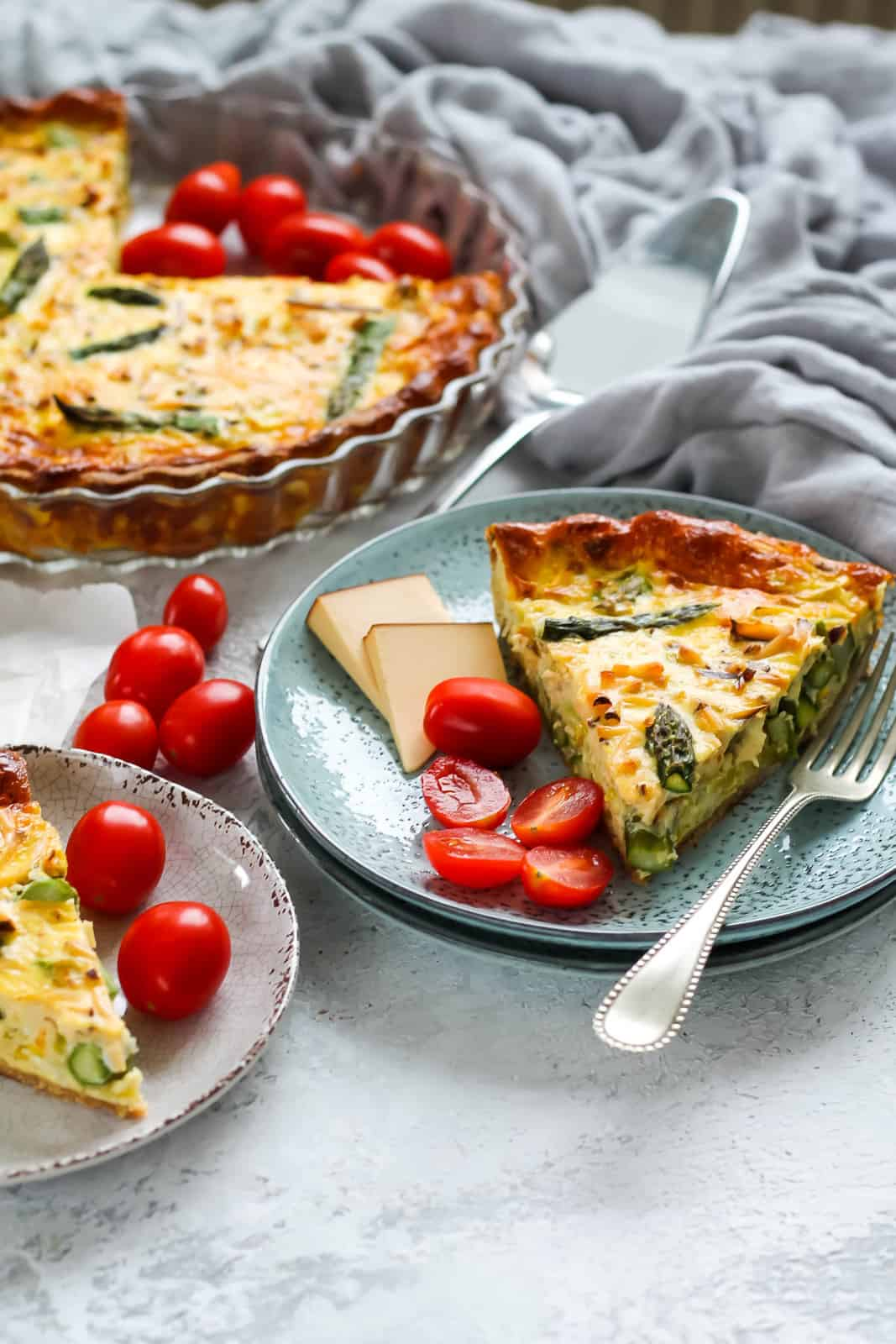 two blue plates with asparagus quiche and sliced cherry tomatoes