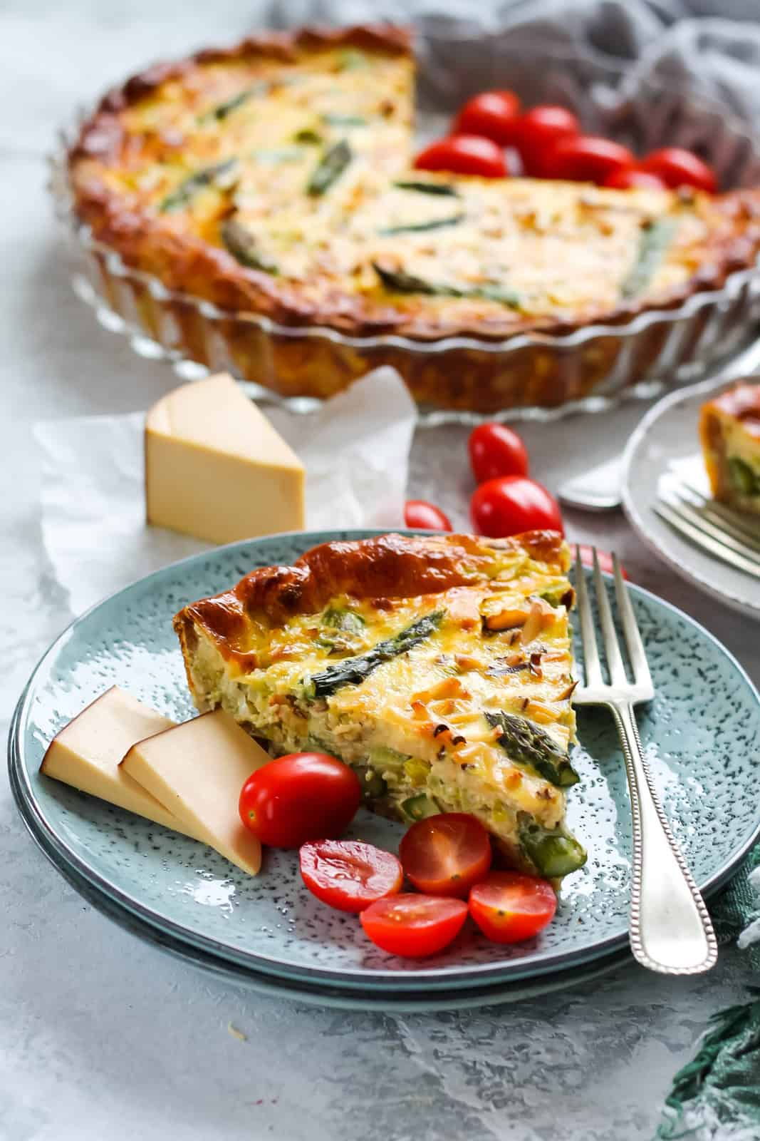 a slice of asparagus quiche on a blue plate with a plate of quiche in the background