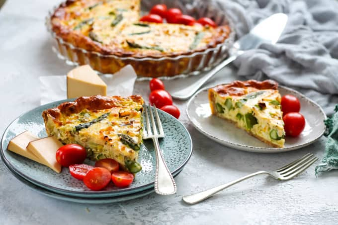 two plates with asparagus quiche, tomatoes, and silver forks