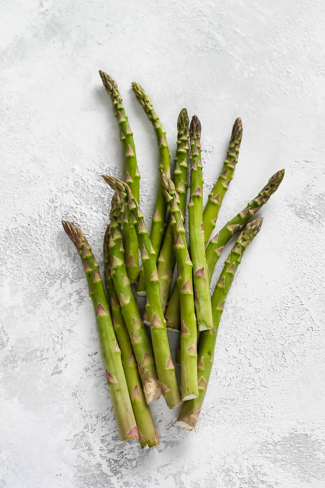 a bunch of asparagus on a grey background