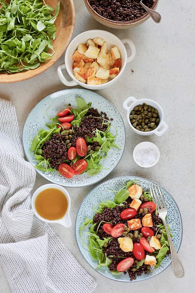 two blue plates of beluga lentil salad on a grey surface