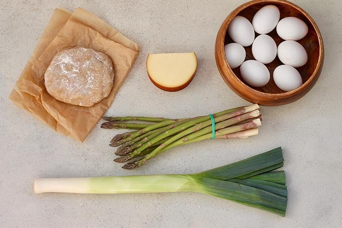 eggs, cheese, asparagus, and leeks on a grey background