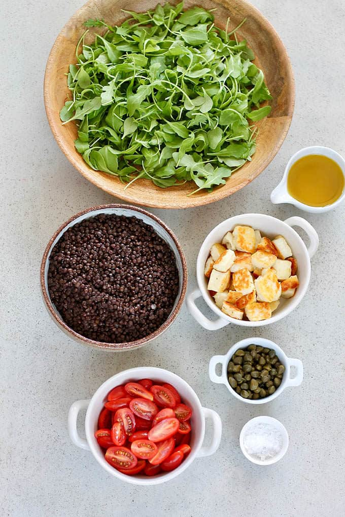 arugula, black lentils, fried halloumi, tomatoes, and capers on a grey background