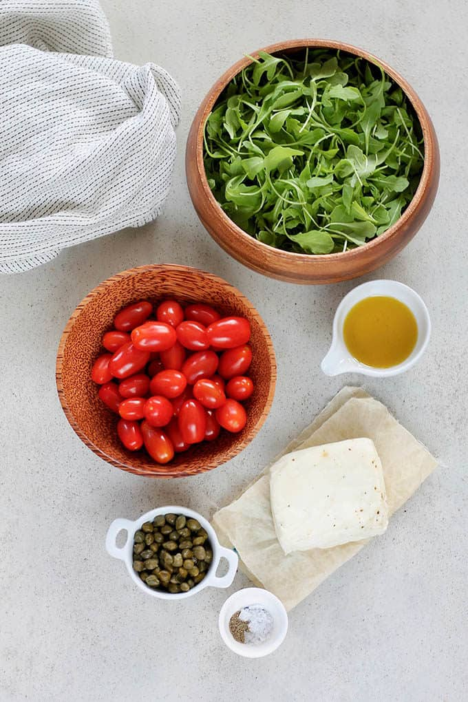 arugula, tomatoes, halloumi, oil, capers, and salt on a grey background