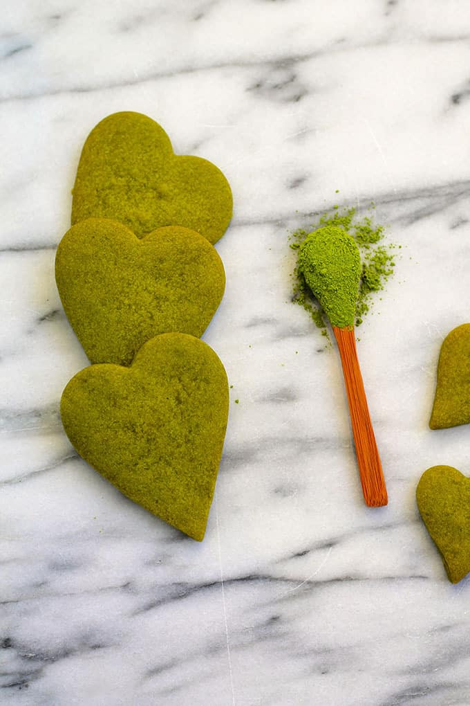 three heart shaped matcha shortbread cookies and a spoon of matcha powder on a marble background