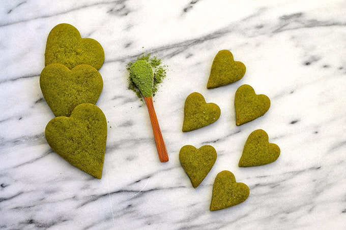 3 large and 6 small heart shaped matcha shortbread cookies on a marble background