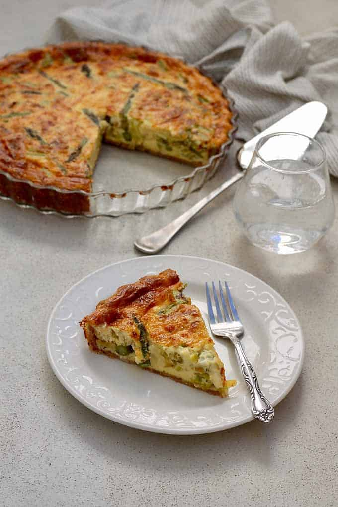 A slice of quiche on a white plate with a fork, a glass of water, full quiche, and server in the background