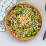 green vegetable pasta topped with hazelnuts in a wooden bowl