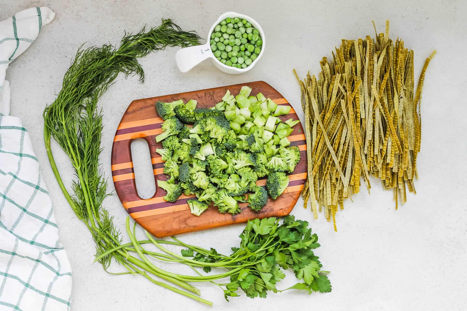 chopped broccoli, frozen peas, fresh herbs, and edamame noodles on a wooden cutting board