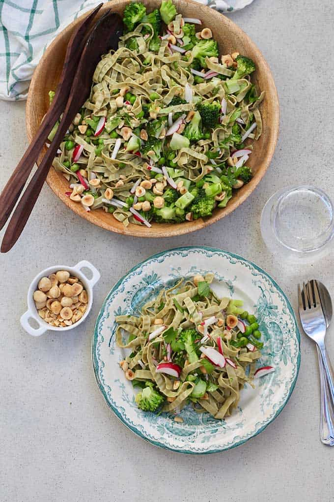 plate of green vegetable pasta on a grey background with a wooden bowl of pasta and a small bowl of chopped nuts beside it