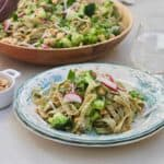 Green vegetable pasta on a printed plate with a glass of water and a bowl of pasta in the background