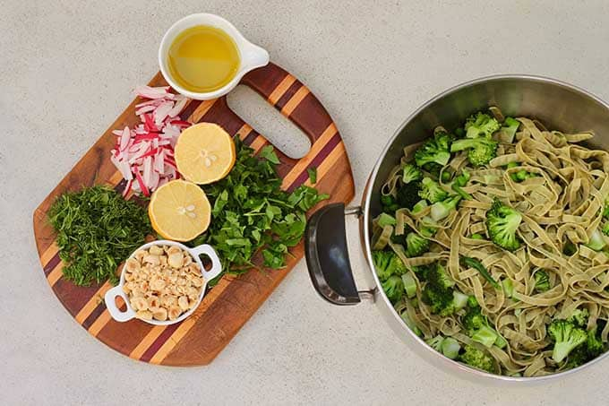 chopped herbs, hazelnuts, lemon, and olive oil on a cutting board beside a pot of green pasta