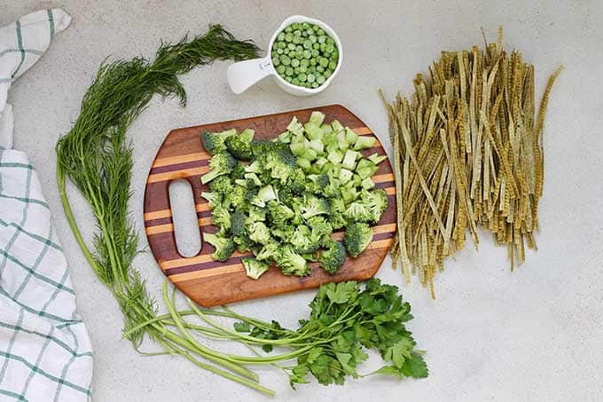 parsley, dill, chopped broccoli, and green bean pasta on a wooden cutting board