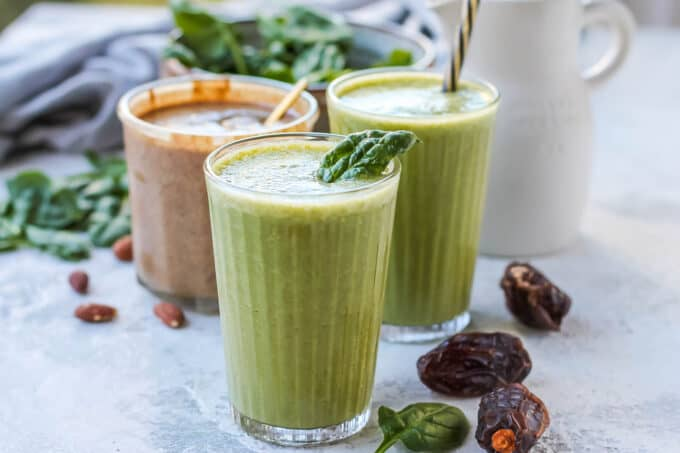 two green smoothies on a grey surface with dates, almonds, and spinach scattered in the background