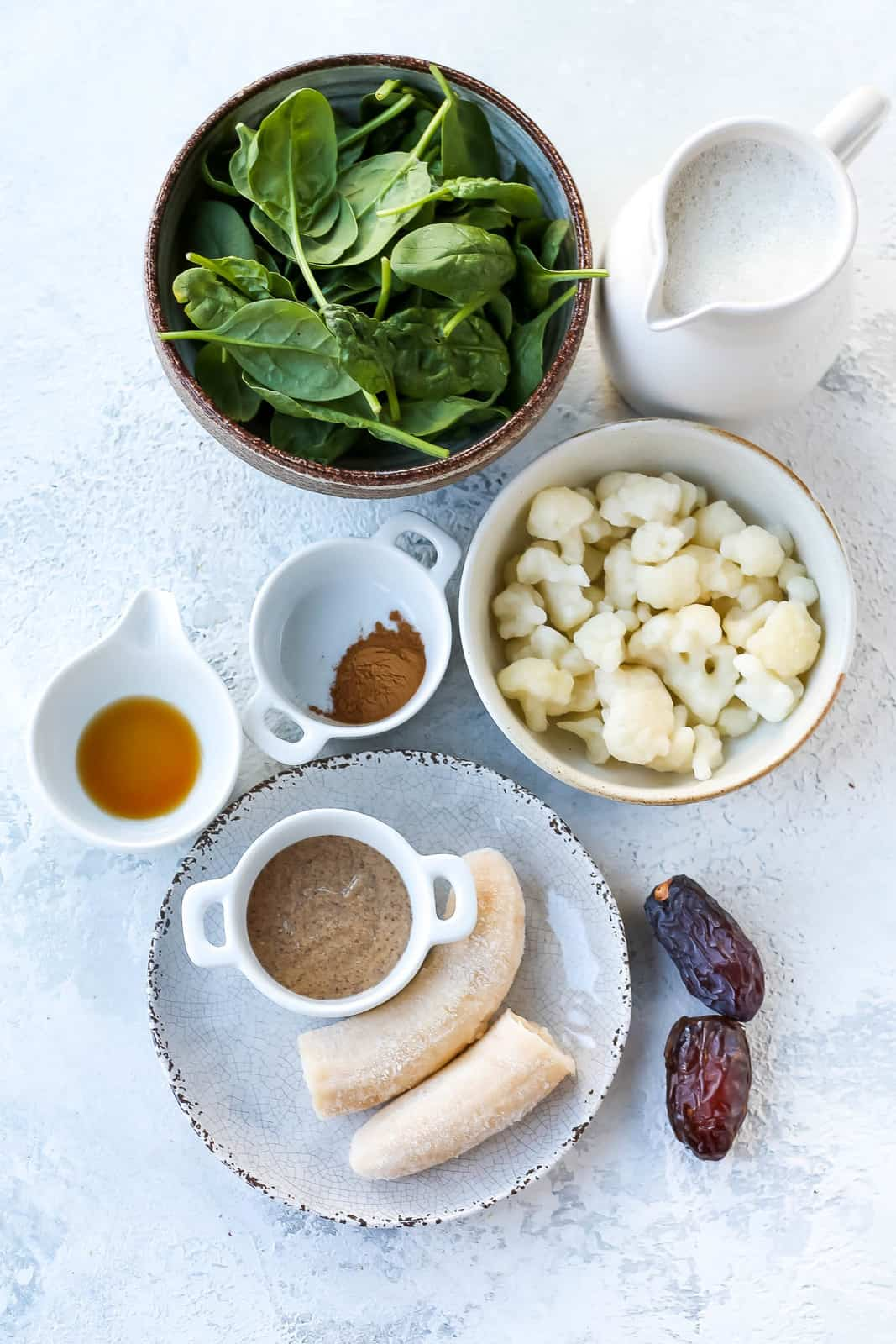 spinach, oat milk, frozen cauliflower, cinnamon, vanilla, almond butter, frozen banana, and dates on a grey background