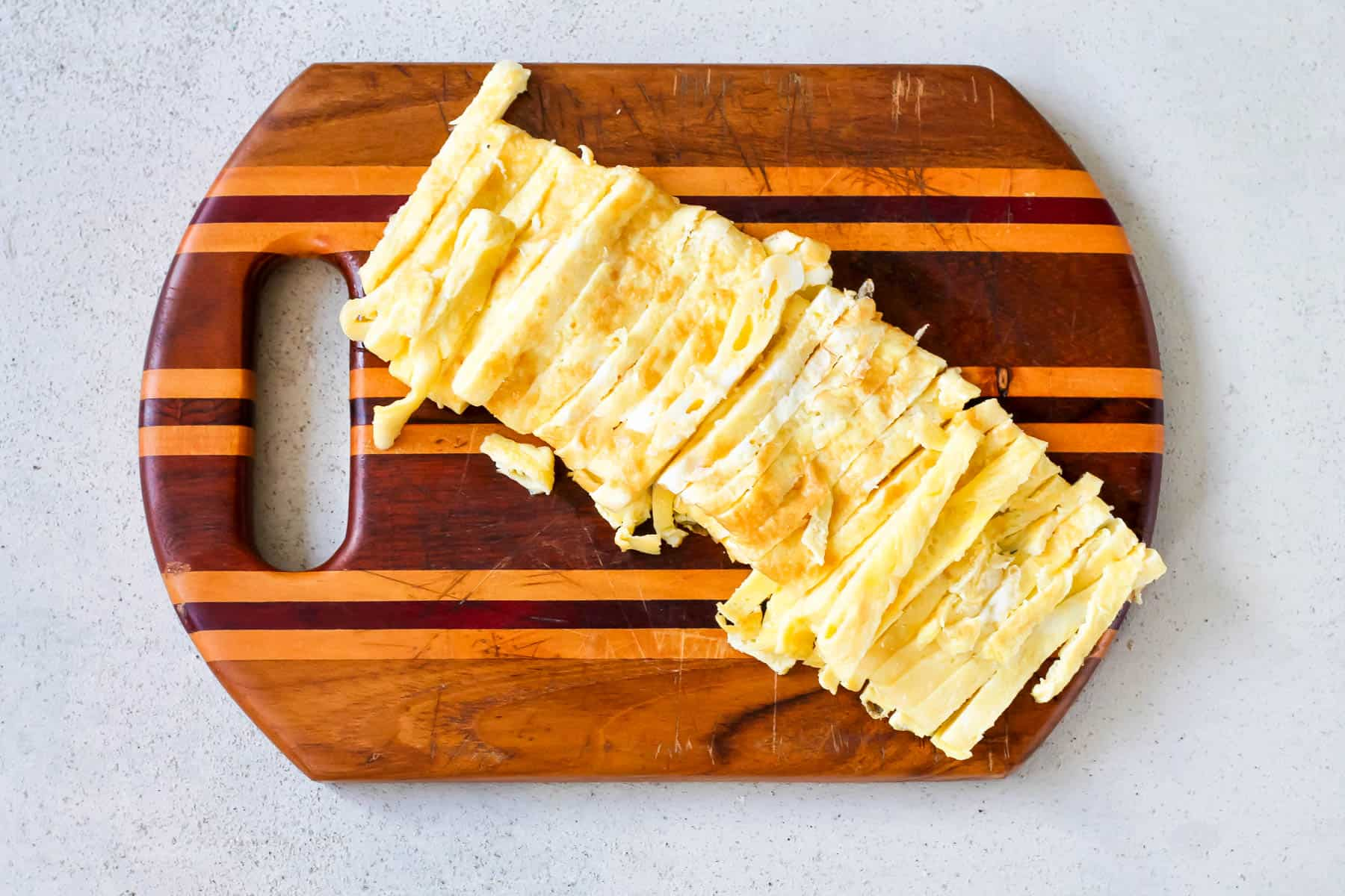 a thinly sliced omelet on a wooden cutting board
