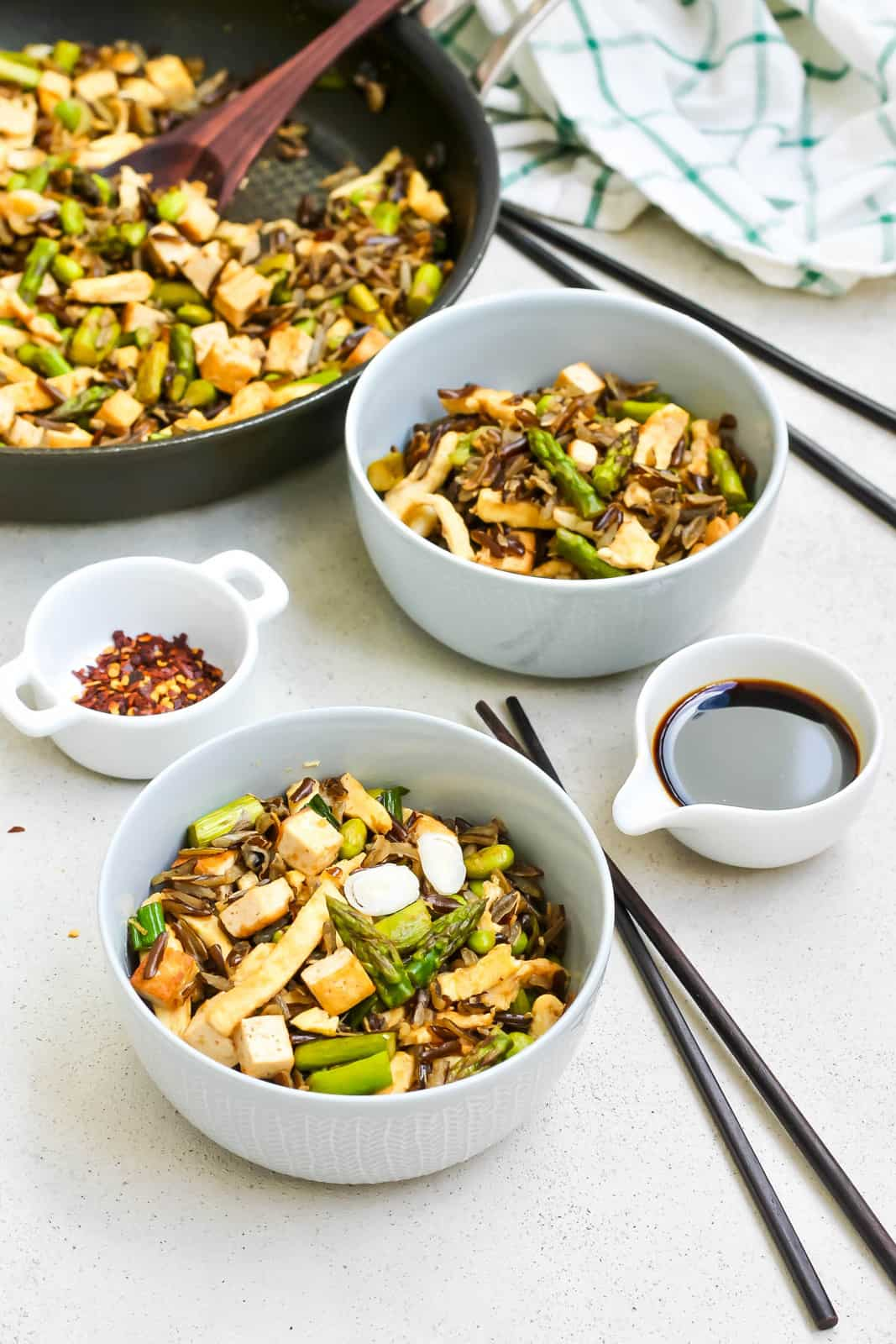 two bowls of asparagus fried rice on a grey background