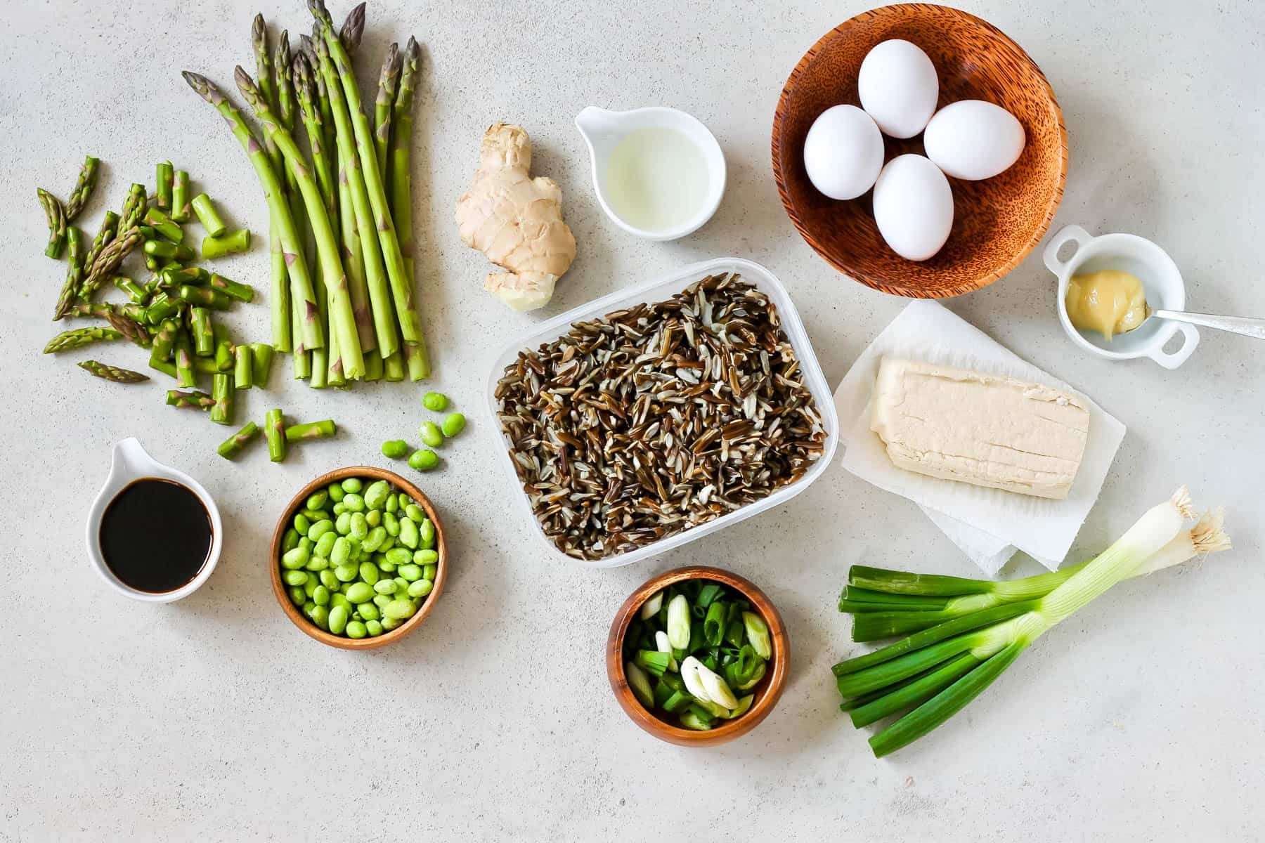 asparagus, wild rice, edamame, eggs, green onion, tofu, ginger, and honey on a grey background