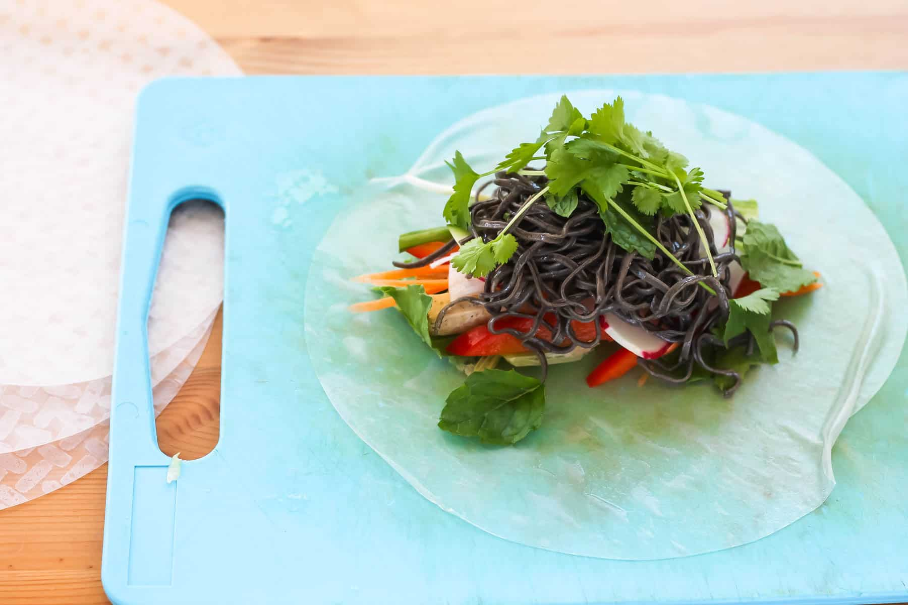 a sheet of rice paper topped with noodles and vegetables on a blue cutting board