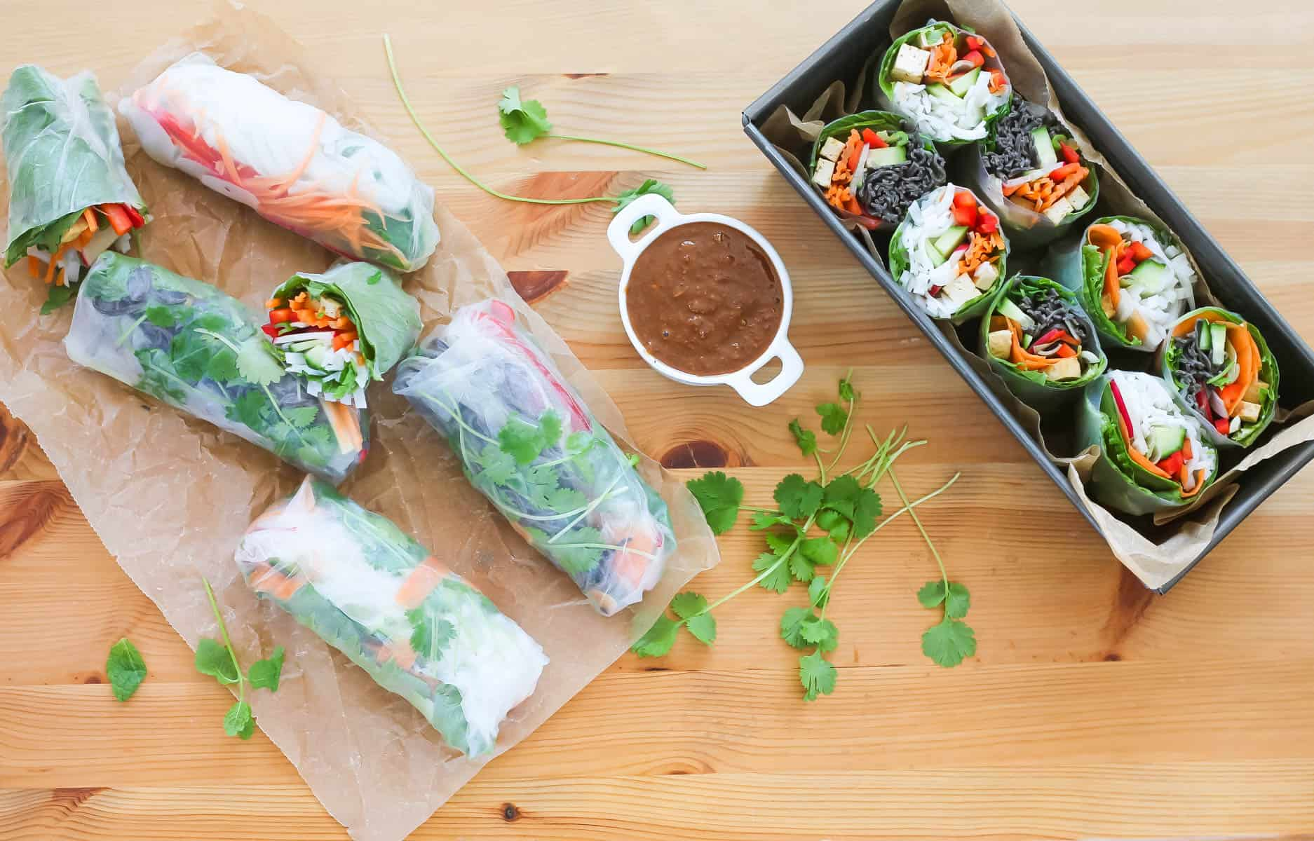 overhead photo of vegetarian rice paper roll in a metal tin with more rolls and herbs scattered in the background