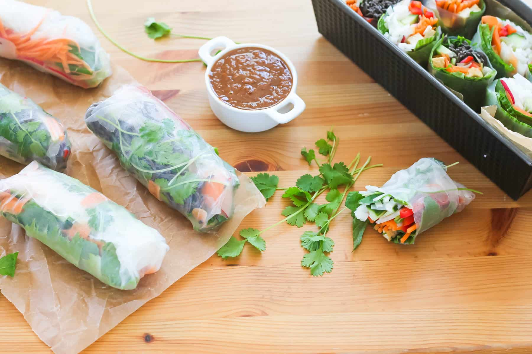 vegetarian rice paper rolls on a wooden background with a white pot of dipping sauce to the side
