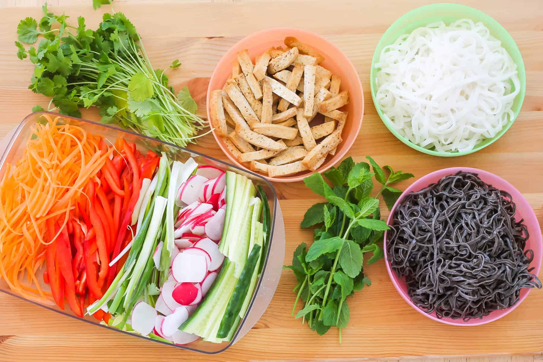baked tofu, rice noodles, black bean noodles, cilantro, mint, and thinly sliced vegetables on a wooden background