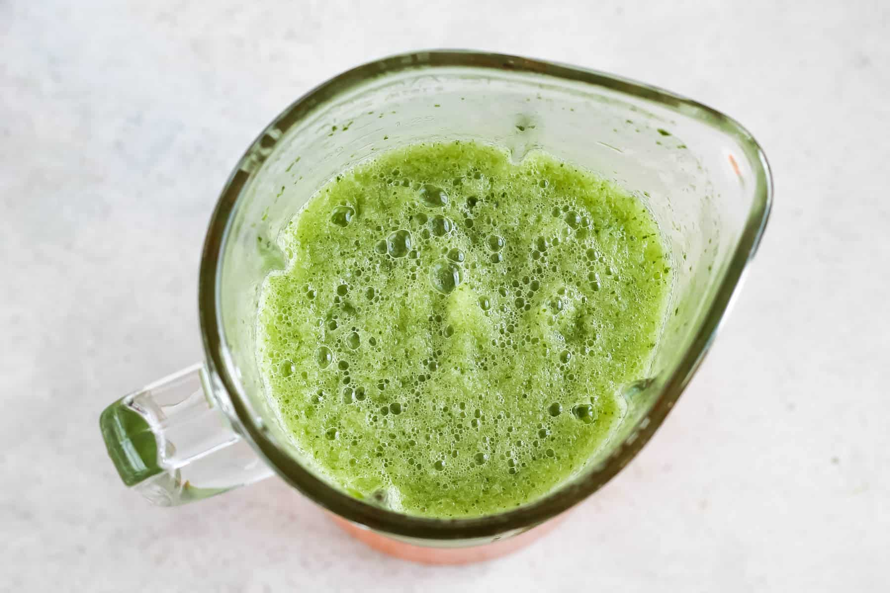 overhead photo of a green slushie in a glass blender