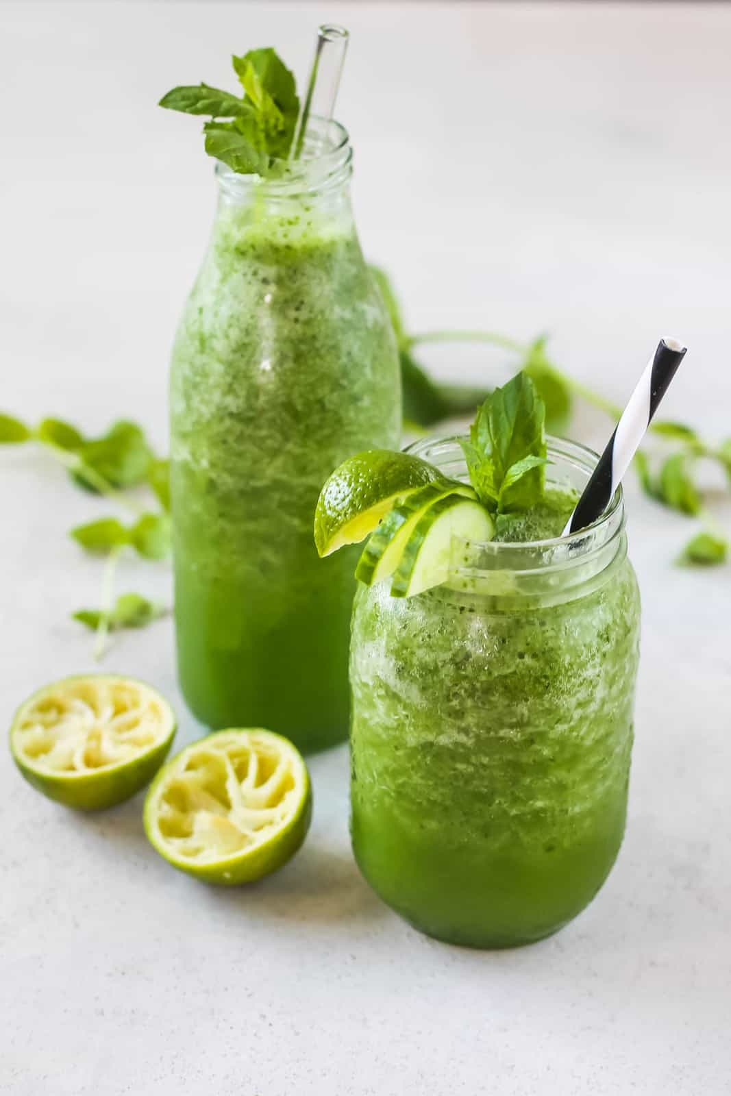 Two glasses filled with bright green cucumber slush with sprigs of mint and slices of lime on top