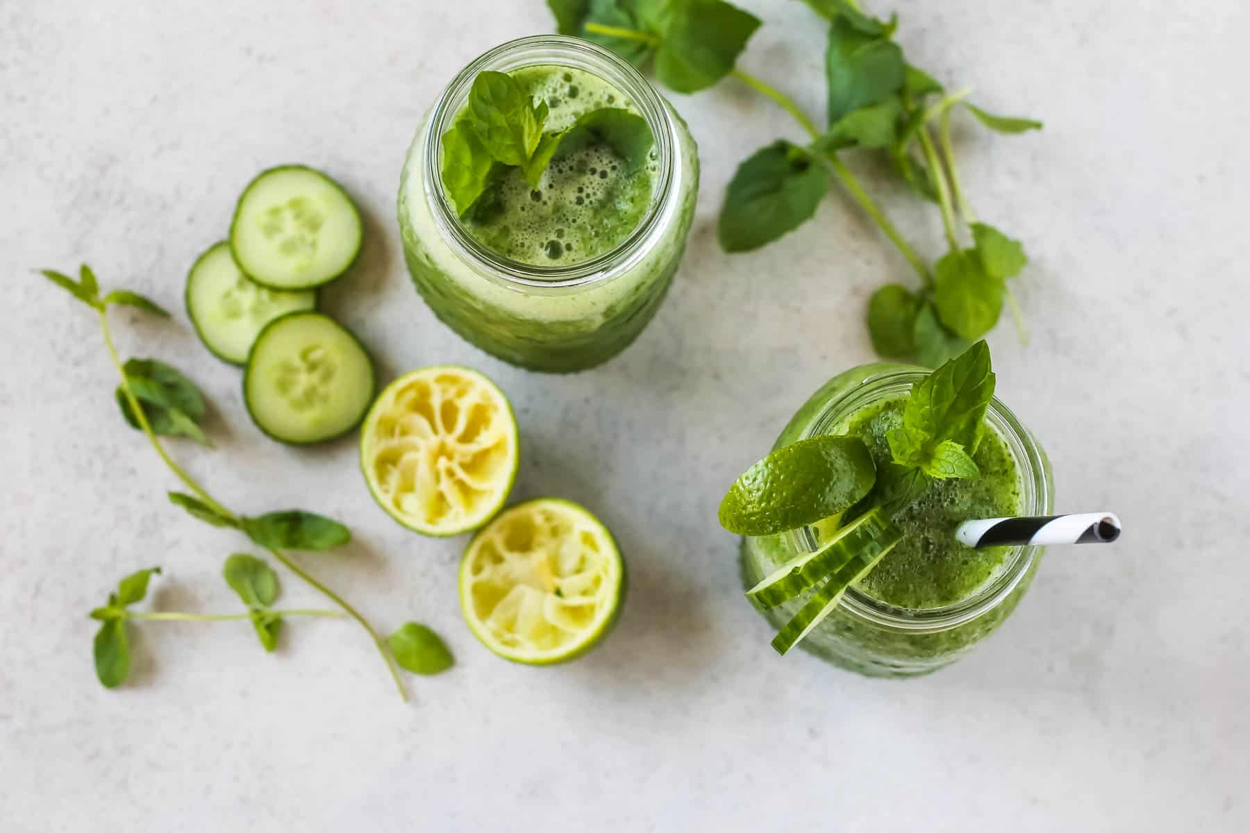 overhead photo of cucumber and mint slushies in clear glasses on a grey background with sprigs of mint and limes to the side