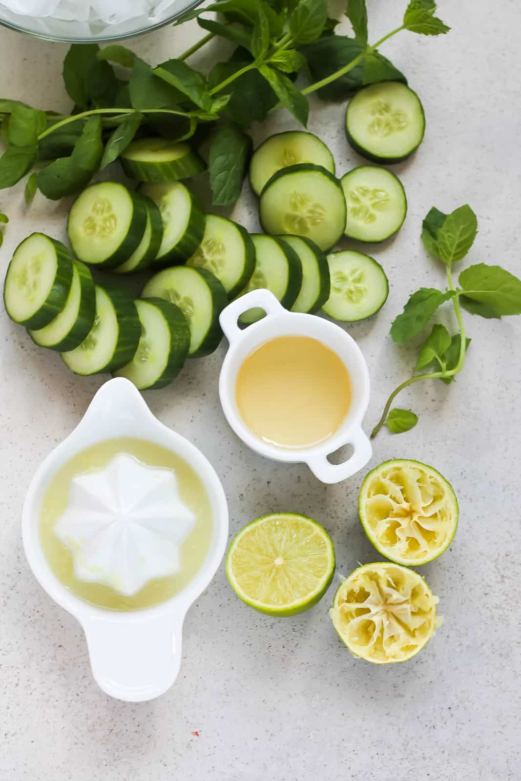 overhead photo with sliced cucumber, mint leaves, juiced limes and lime juice, honey, and a bowl of ice on a grey background