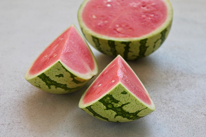 a sliced watermelon on a grey background