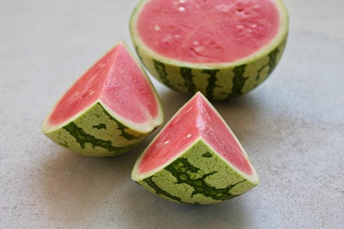 a sliced watermelon on a grey background