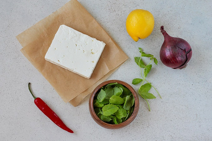 feta, chili, mint, lemon, and a red onion on a grey background