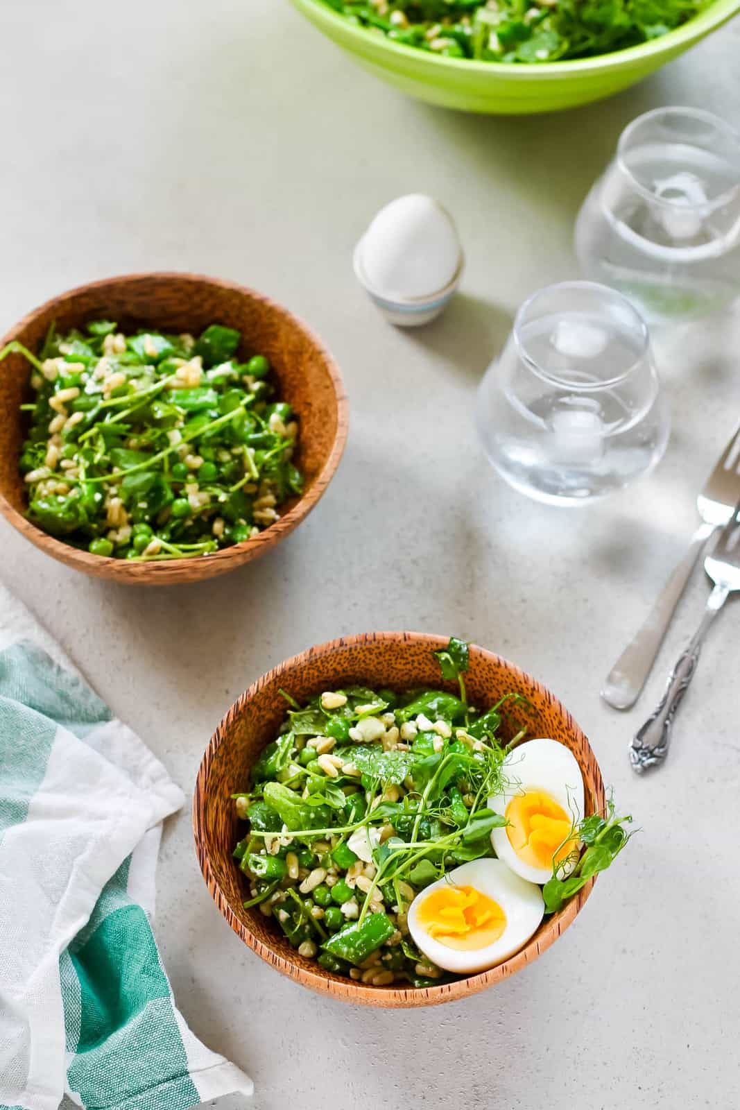 two wooden salad bowls with green pea salad and a hard boiled egg in an egg cup
