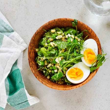green pea salad in a wooden salad bowl with a green and white napkin to the side