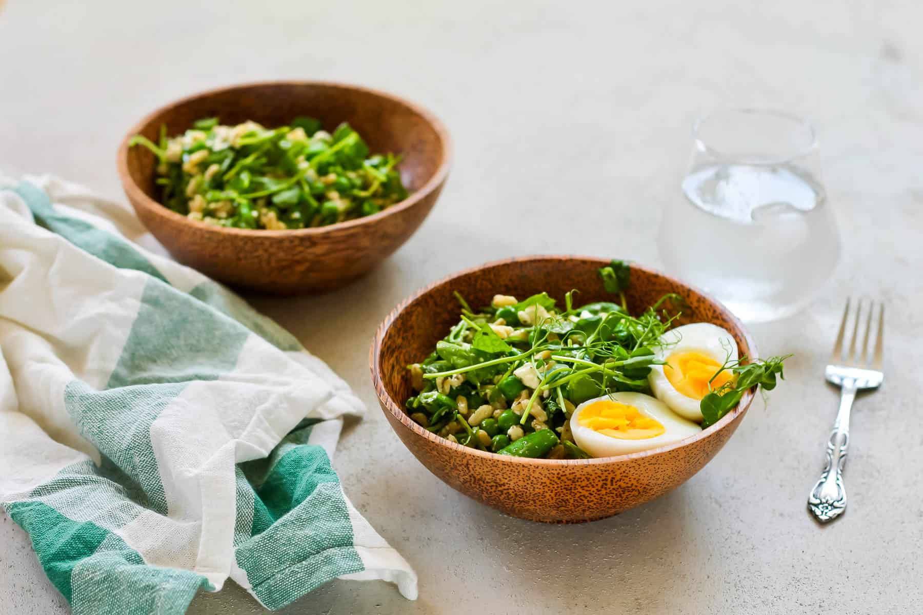 two wooden bowls with green pea salad on a grey background
