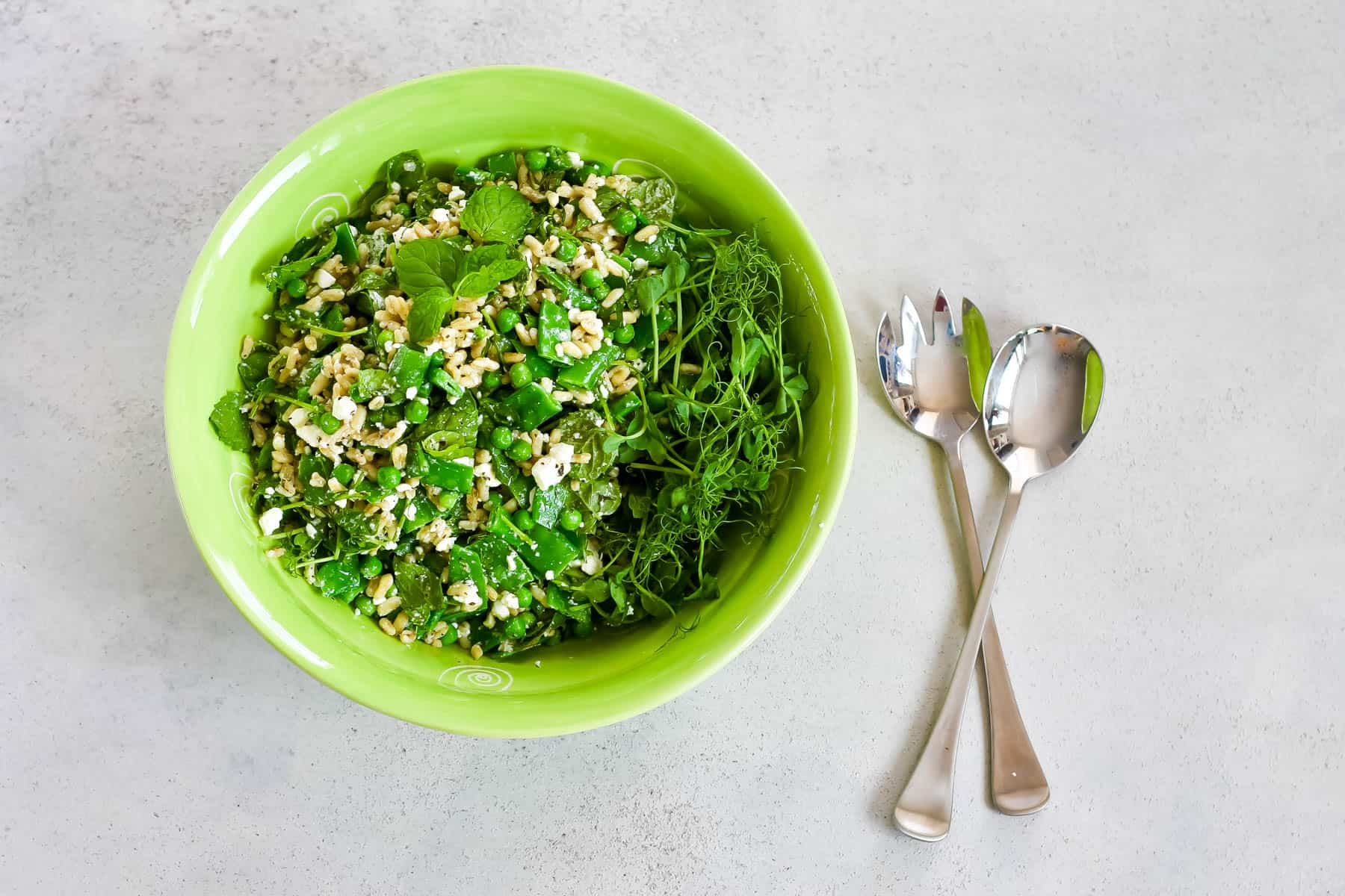 overhead photo of a green pea salad with feta and mint in a large green salad bowl
