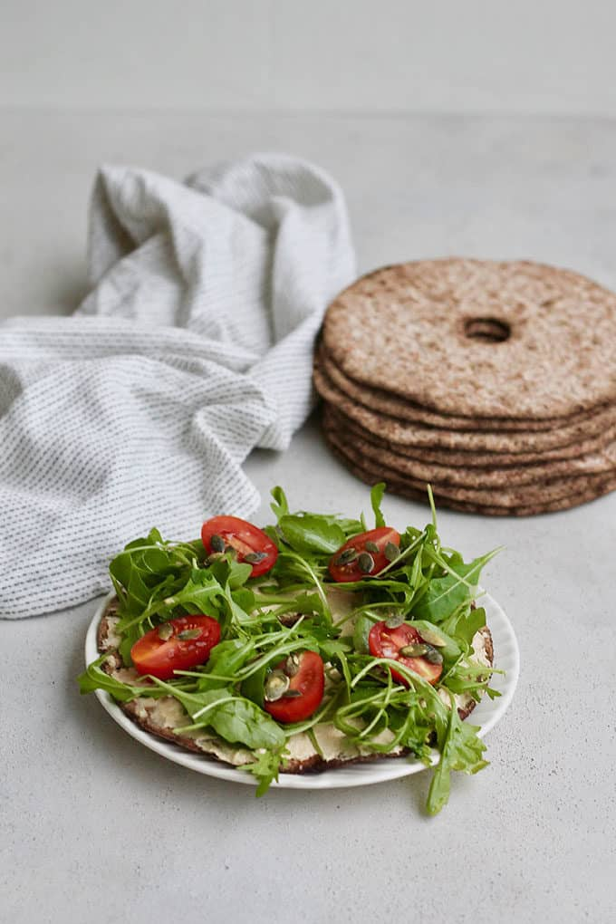 A stack of round rye crispbread, a white tea towel, and a rye crisp bread topped with hummus, tomatoes, and arugula