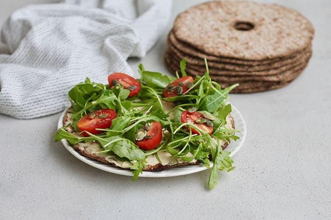 A round rye crispbread topped with hummus and salad to make an open faced hummus sandwich