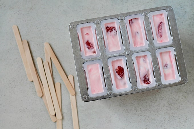 Strawberry yoghurt popsicle mix poured into popsicle moulds