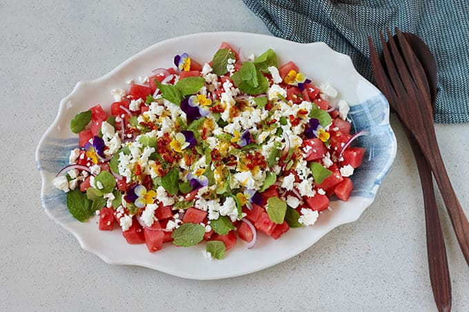 watermelon and feta salad on a blue and white platter with a dark grey dishcloth to the side