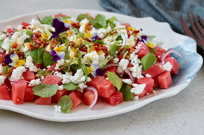 watermelon and feta salad topped with edible flowers on a blue and white platter