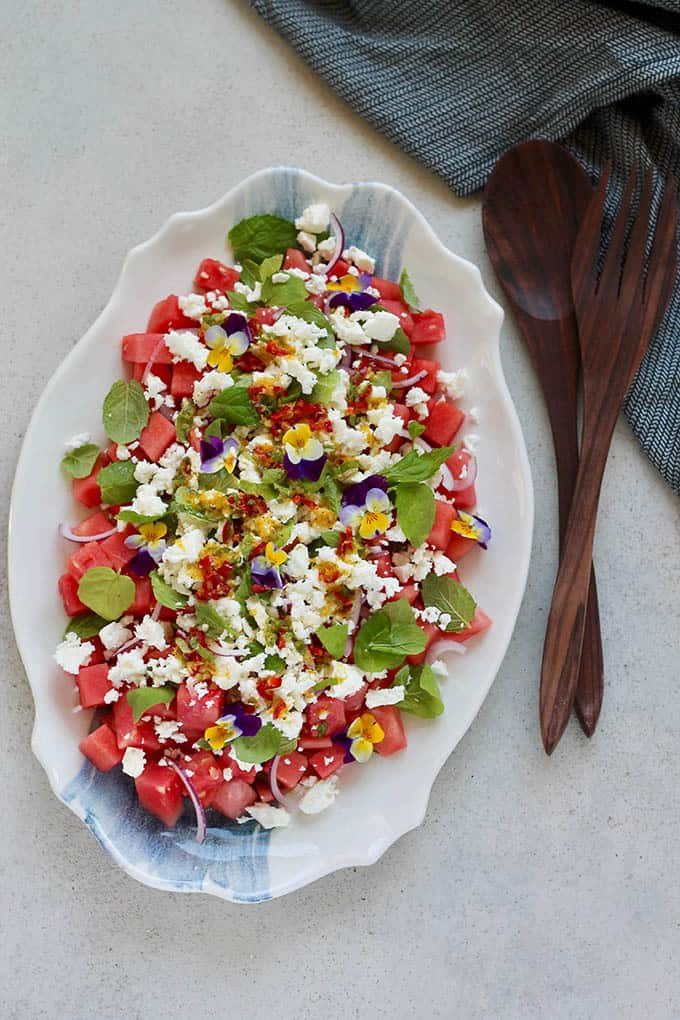 portrait shot of a watermelon and feta salad topped with edible flowers on a blue and white platter, with a set of wooden salad servers to the side