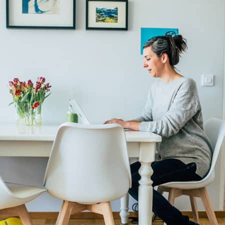 woman sitting at table on the computer