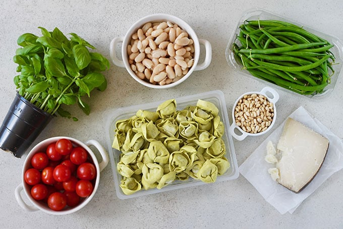 basil, tomatoes, beans, tortellini, pine nuts, pecorino, and green beans on a grey background