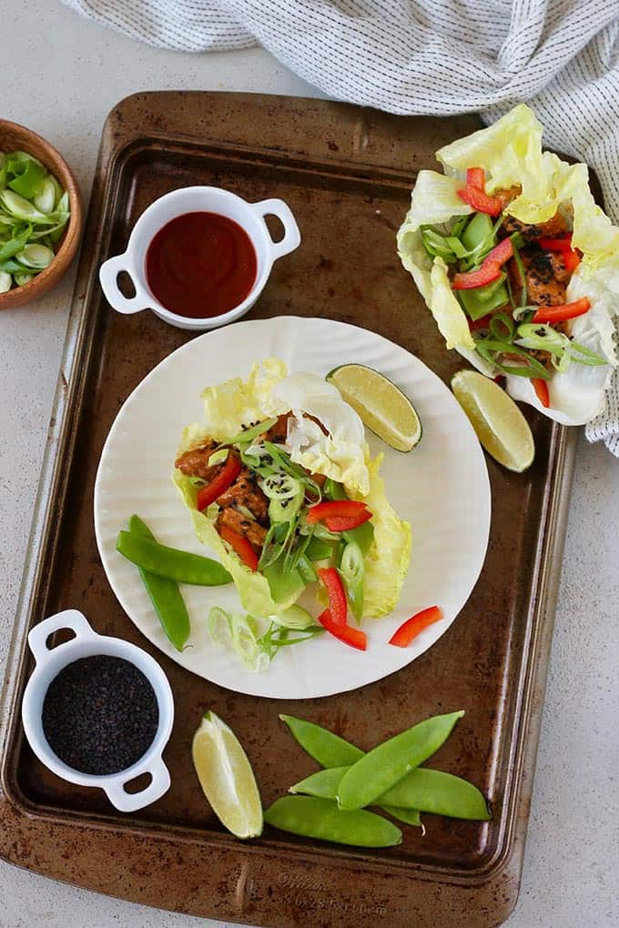 vegetarian lettuce wraps on a metal tray with extra vegetables and sauce to the side