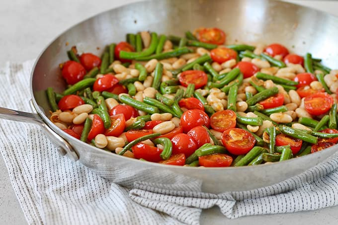 Tomatoes, green beans, and cannelini beans in a skillet.
